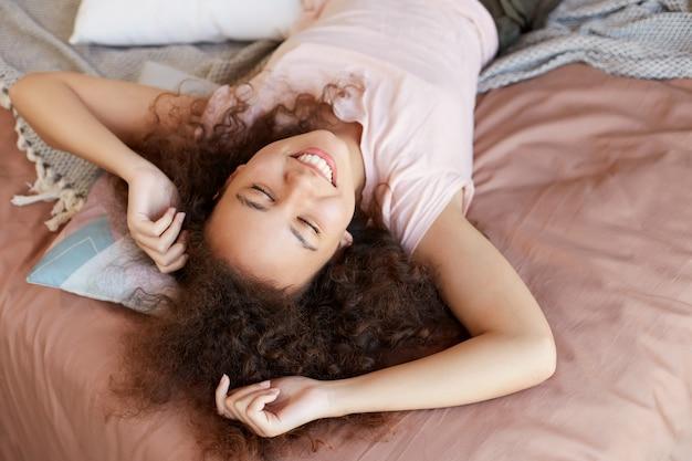 Junge träumende afroamerikanerin genießt den sonnigen tag zu hause, verbringt ihren freien tag und ruht sich zu hause aus, liegt auf dem bett und lächelt breit, wünscht sich ein wochenende.