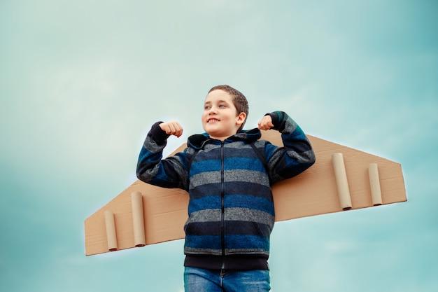 Junge träumt davon, flieger zu werden. kind, das mit flügelflugzeug spielt