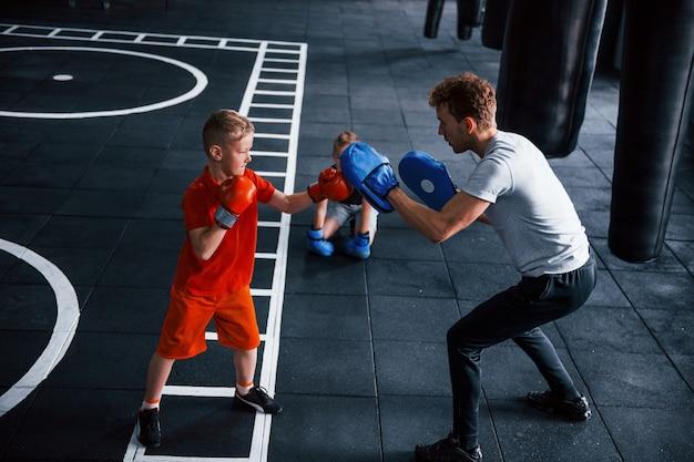 Junge trainer unterrichtet kinder boxsport in der turnhalle.