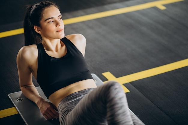 Junge trainerin, die im fitnessstudio trainiert