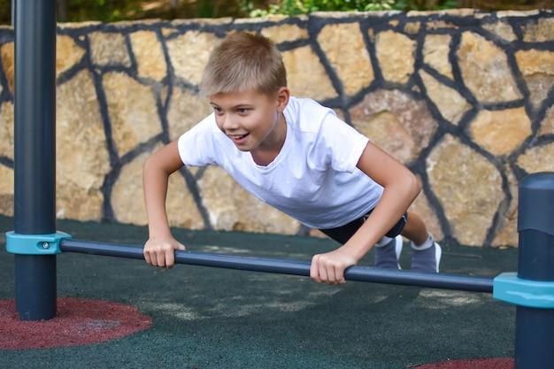 Junge trainiert auf dem outdoor-sport-simulator. sportkind im sommer auf spielplatz.
