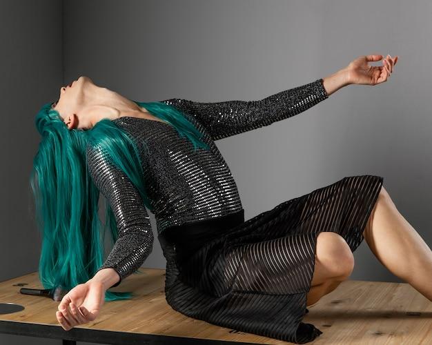 Junge transgender-person, die grüne perücke long shot trägt