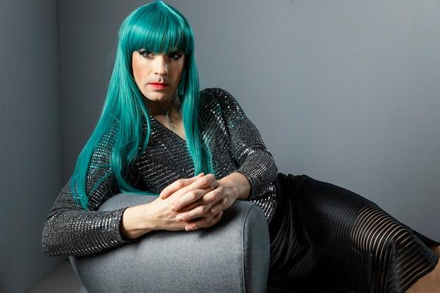 Junge transgender-person, die grüne perücke trägt, die auf der couch sitzt