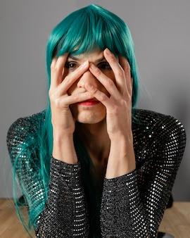 Junge transgender-person, die grünes perückenporträt trägt