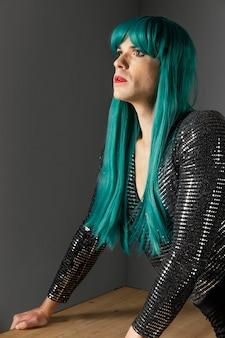 Junge transgender-person, die seitenansicht der grünen perücke trägt