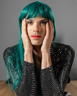 Junge transgender-person, die vorderansicht der grünen perücke trägt