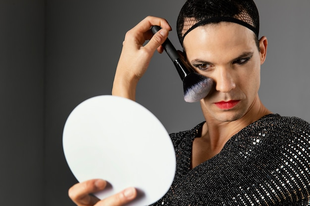 Junge transgender-person mit einem make-up-pinsel