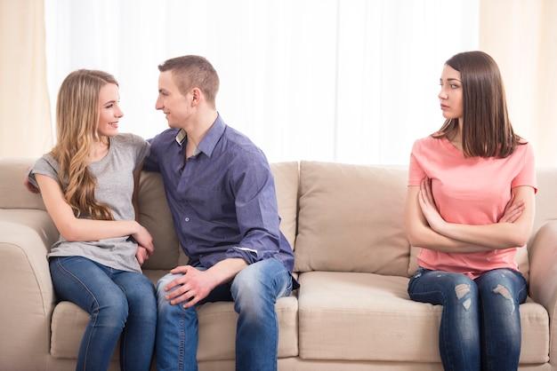 Junge traurige frau, die auf der couch sitzt.
