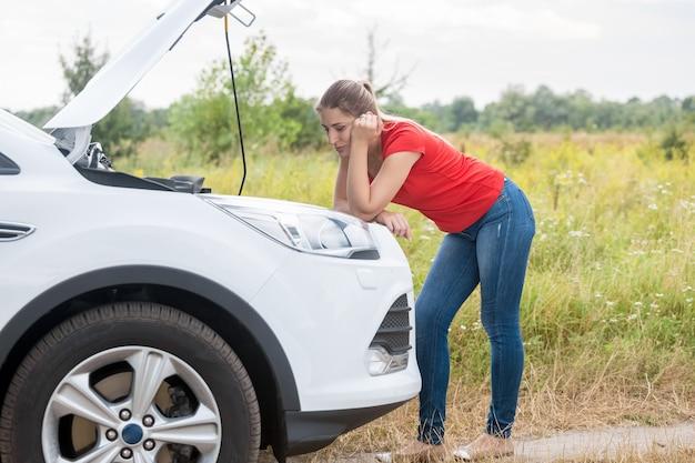 Junge traurige frau, die kaputtes auto betrachtet und auf hilfe auf der landstraße wartet