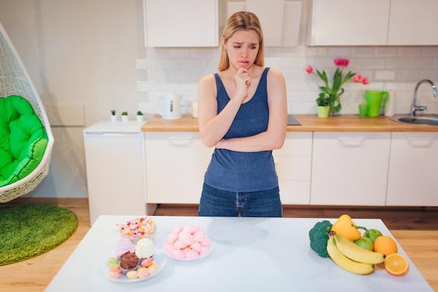 Junge traurige frau im blauen t-shirt, das zwischen gesundem und ungesundem essen in der küche wählt