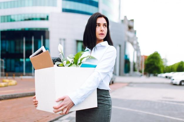 Junge traurige geschäftsfrau im büro siut mit einer schachtel ihrer büromaterialien mit geschäftszentrum am hintergrund. arbeitslosigkeit, finanzkrise