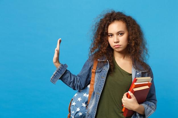 Junge traurige studentin in jeanskleidung und rucksack hält bücher isoliert auf blauer wand