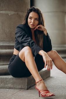Junge trendige frau posiert in shorts und jacke auf der straße