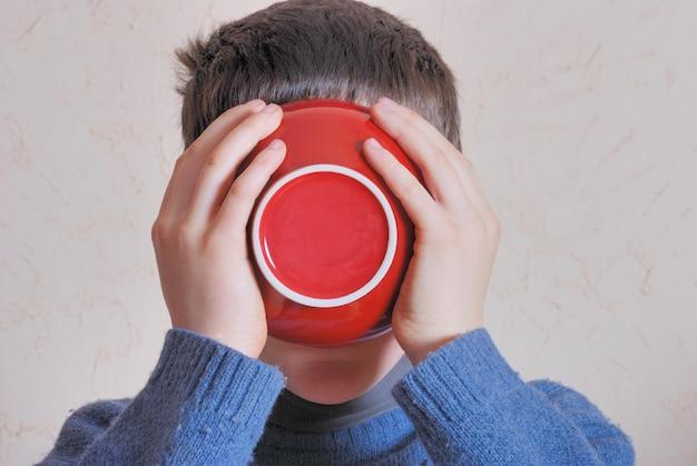 Junge trinkt aus der schüssel