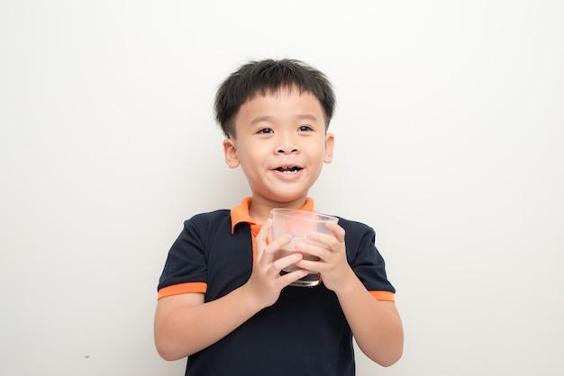 Junge trinkt schokoladenmilch isoliert auf weißem wandhintergrund.