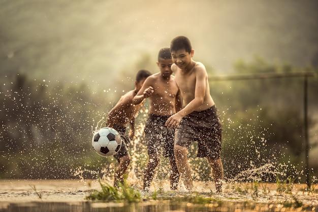 Junge tritt einen fußball (fokus auf fußball)