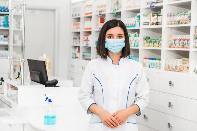 Junge türkische apothekerin mit medizinischer maske, die vor zähler in der apotheke steht