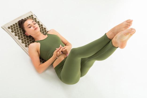 Junge turnerin mit athletischem körper liegt auf einer sportmatte und meditiert