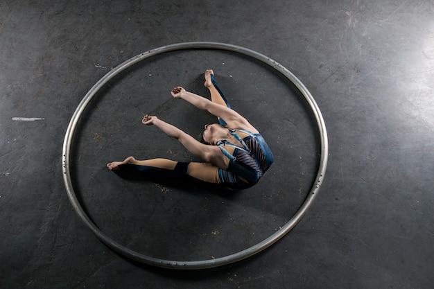 Junge turnerin mit schwarzem haar, die flexible tricks im großen reifen auf grauem hintergrund macht