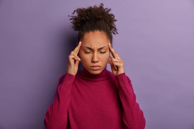 Junge überarbeitete frau schließt die augen und berührt die schläfen, leidet unter kopfschmerzen oder migräne, fühlt sich unwohl und krank, versucht sich zu beruhigen und geduldig zu sein, braucht schmerzmittel, steht drinnen, ist lässig gekleidet