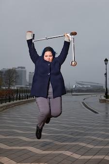 Junge übergewichtige frau mit blauen haaren im freizeitmantel springt auf promenade mit roller in ihren händen.