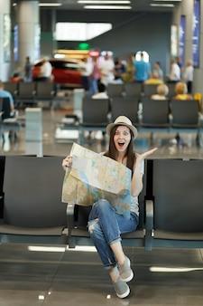 Junge überglückliche reisende touristenfrau mit papierkarte, route suchen, hände verteilen, in der lobbyhalle am flughafen warten wait