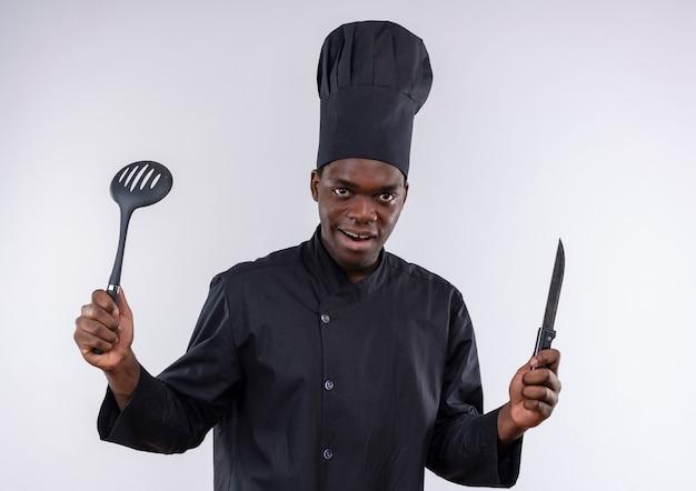 Junge überraschte afroamerikanische köchin in der kochuniform hält messer und spatel auf weiß mit kopienraum