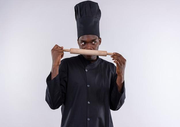 Junge überraschte afroamerikanische köchin in der kochuniform hält nudelholz und schaut zur seite auf weiß mit kopienraum