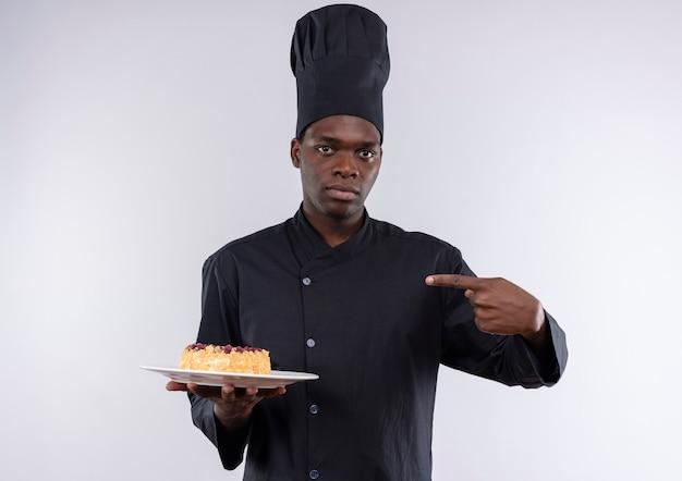 Junge überraschte afroamerikanische köchin in der kochuniform hält und zeigt auf kuchen auf teller auf weiß mit kopienraum