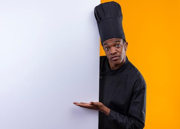 Junge überraschte afroamerikanische köchin in der kochuniform steht hinter weißer wand und zeigt auf wand mit hand lokalisiert auf orange wand