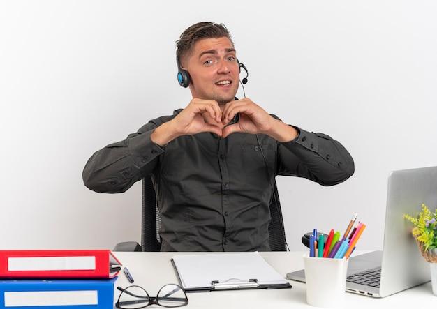 Junge überraschte blonde büroangestellte mann auf kopfhörern sitzt am schreibtisch mit bürowerkzeugen unter verwendung von laptopgestures-herzhandzeichen lokalisiert auf weißem hintergrund mit kopienraum