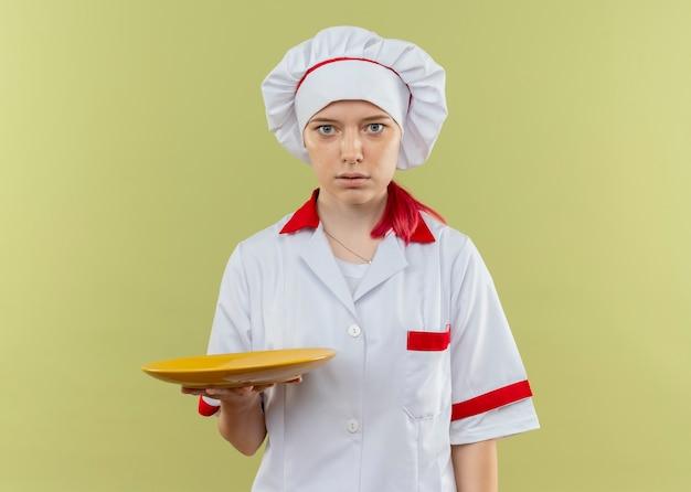 Junge überraschte blonde köchin in kochuniform hält teller und sieht auf grüner wand isoliert aus