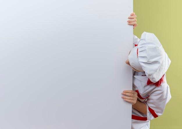 Junge überraschte blonde köchin in kochuniform steht hinter und betrachtet weiße wand lokalisiert auf grüner wand