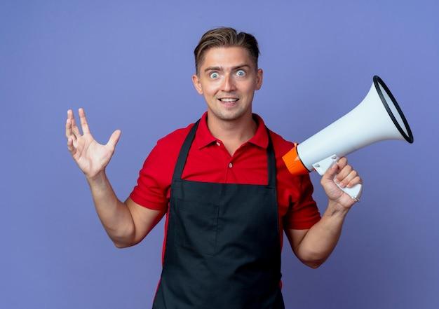 Junge überraschte blonde männliche friseur in uniform hält lautsprecher und hebt hand isoliert auf violettem raum mit kopierraum