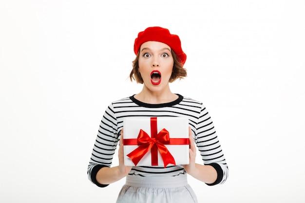 Junge überraschte dame, die geschenküberraschungskasten hält.