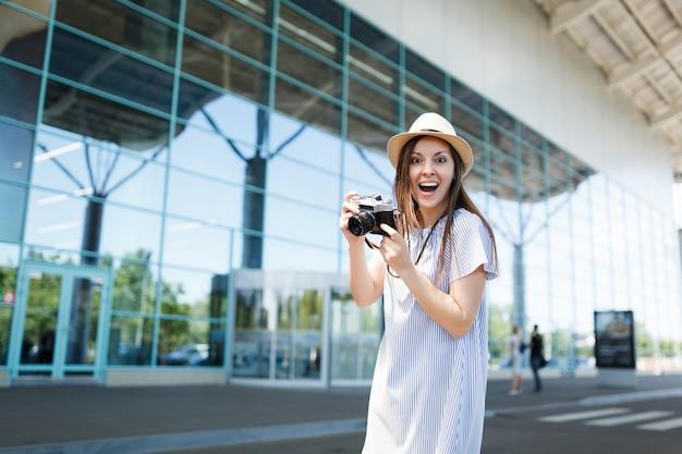 Junge überraschte freudige reisende touristenfrau mit hut, die retro-vintage-fotokamera am internationalen flughafen hält