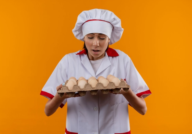 Junge überraschte kaukasische köchin in der kochuniform hält und betrachtet charge von eiern auf orange mit kopienraum