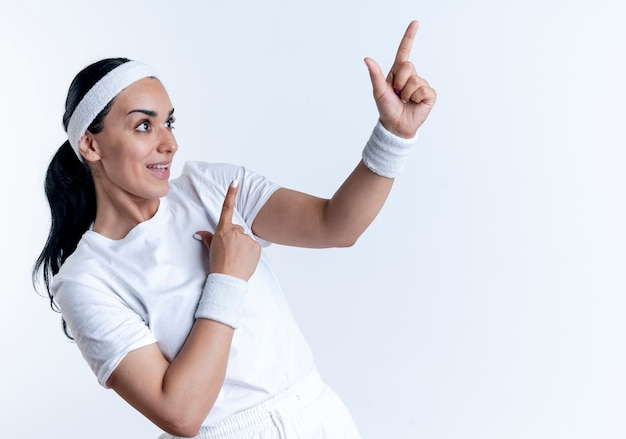 Junge überraschte kaukasische sportliche frau, die stirnband und armbänder trägt, schaut und zeigt zur seite lokalisiert auf weißem raum mit kopienraum