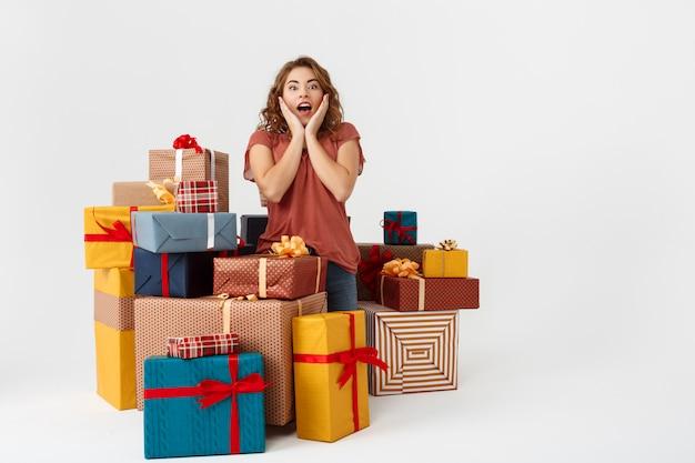 Junge überraschte lockige frau unter geschenkboxen