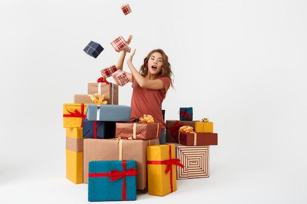 Junge überraschte lockige frau unter lügenden und fallenden geschenkboxen