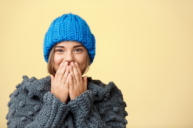 Junge überraschte schöne blonde frau in strickmütze und pullover auf gelb.