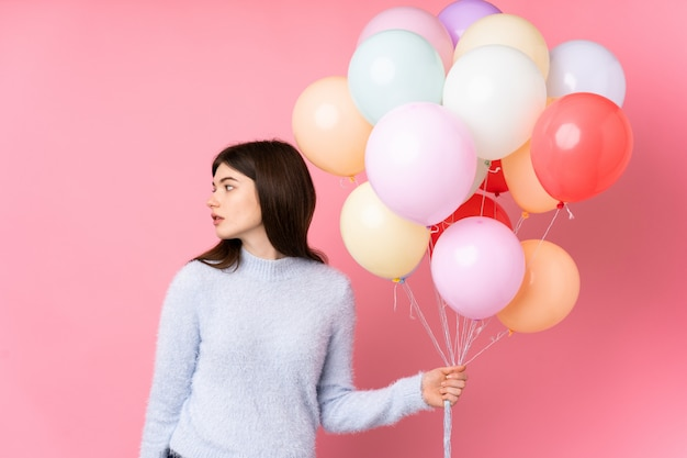 Junge ukrainische jugendlichfrau, die viele ballone über der lokalisierten rosa wand schaut seite hält