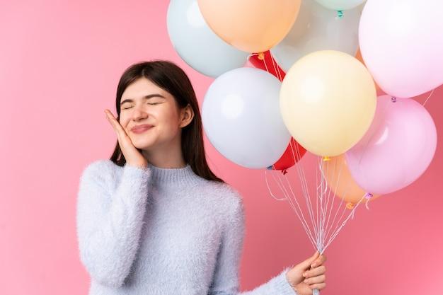 Junge ukrainische jugendlichfrau, die viele ballone über lokalisierter rosa wand hält