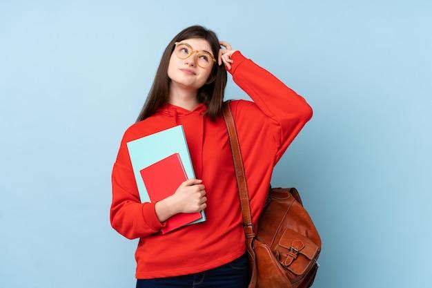 Junge ukrainische jugendlichstudentenfrau, die einen salat über der lokalisierten blauen wand hat zweifel mit verwirren gesichtsausdruck hält