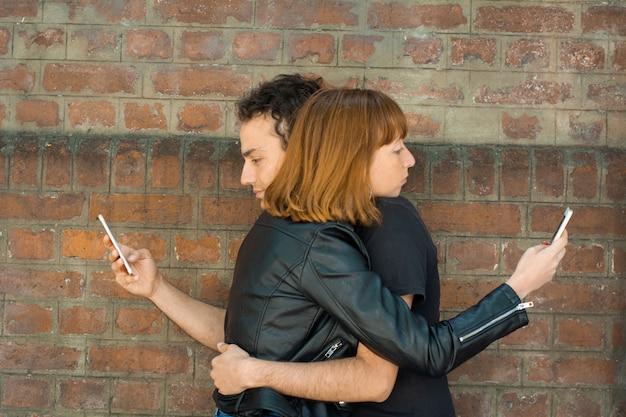 Junge umarmende paare, während jedes entlang ihres eigenen smartphone anstarrt.