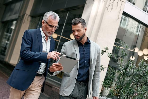 Junge und ältere geschäftsleute, die draußen auf dem stadthintergrund digitale tablette verwenden