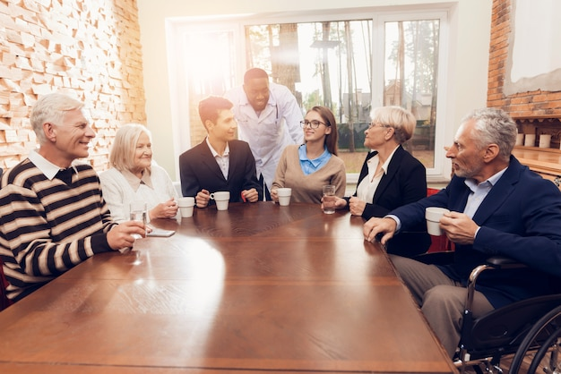 Junge und alte leute sitzen zusammen im raum des pflegeheims