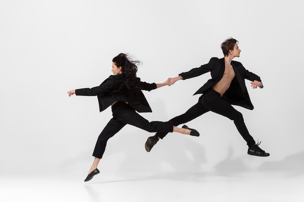 Junge und anmutige balletttänzer im minimalen schwarzen stil lokalisiert auf weiß
