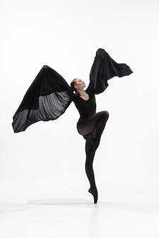 Junge und anmutige balletttänzerin im minimalistischen schwarzen stil isoliert auf weiß