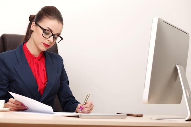 Junge und attraktive geschäftsfrau, die im büro arbeitet